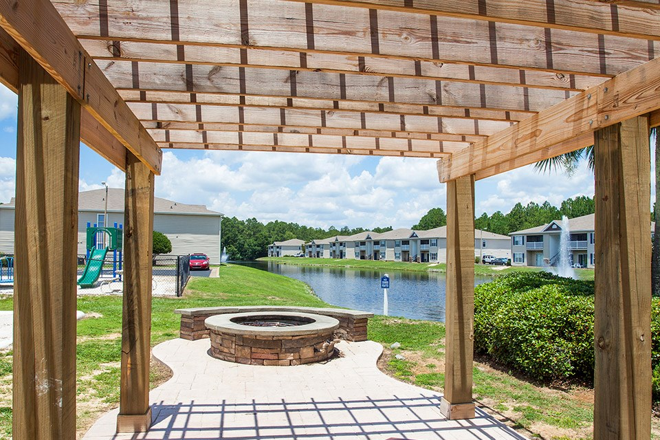 An overhang gives protection from the sun next to the lakeside fire pit area at Crystal Lake Apartments in Pensacola, FL